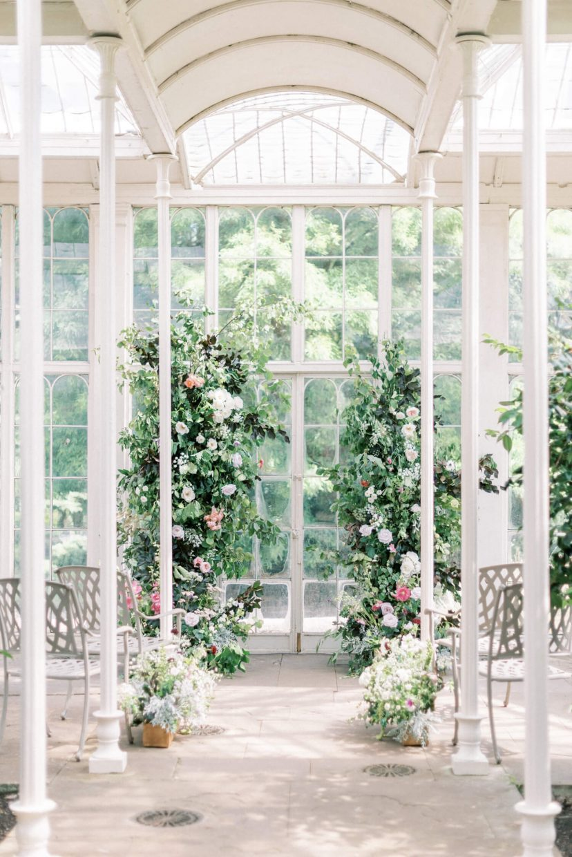 spring summer wedding ceremony aisle with floral installation and flower pillars filled with david austin english british grown roses in light bright and airy wetting - Venue: Wollaton Hall Camellia House (cast iron glass house) in Nottinghamshire. Photo by London and Newcastle UK based Filipina fine art light bright and airy wedding and portrait photographer Cristina Ilao, more at www.cristinailao.com