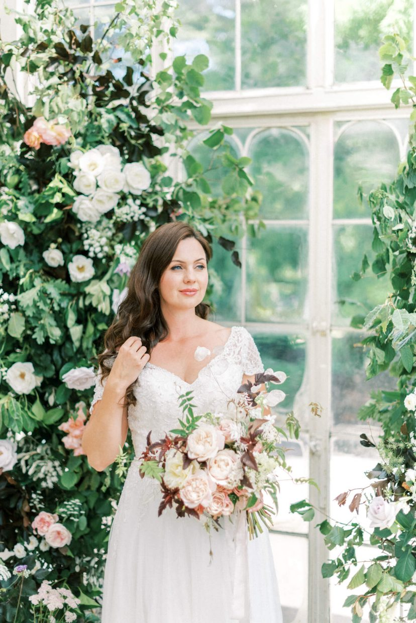 brunette bride smiling while holding a spring summer bouquet with karge david austin english roses in pink and peach, neutral foxgloves and clematos handpicked from the garden; sweetheart neckline wedding gown with sequins and tulle full a line skirt; - Venue: Wollaton Hall Camellia House (cast iron glass house) in Nottinghamshire. Photo by London and Newcastle UK based Filipina fine art light bright and airy wedding and portrait photographer Cristina Ilao, more at www.cristinailao.com