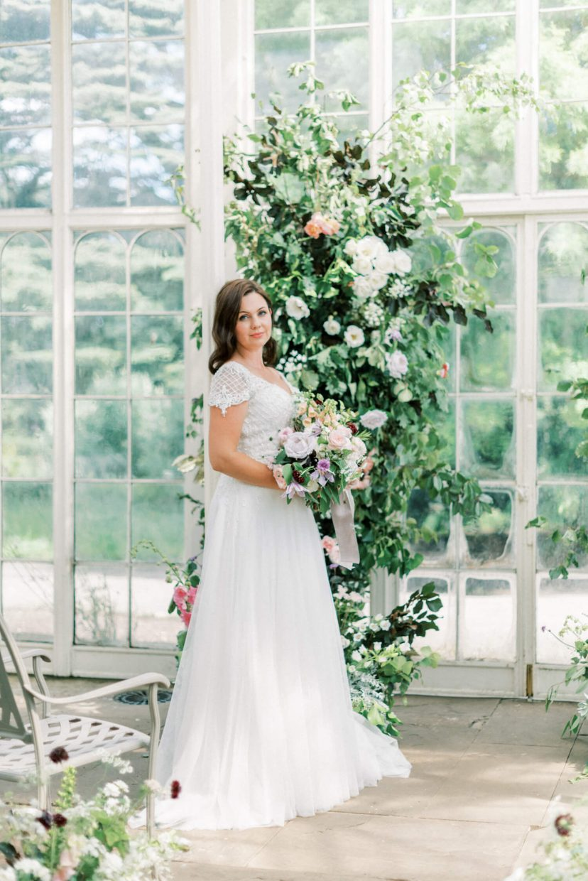 bride standing while leaning on a white cast iron pillar, wearing a white sweetheart neckline sequined wedding dress with full tulle skirt and spring bridal bouquet of large david austin roses, clematis, foxgloves and meadow garden handpicked style flowers - Venue: Wollaton Hall Camellia House (cast iron glass house) in Nottinghamshire. Photo by London and Newcastle UK based Filipina fine art light bright and airy wedding and portrait photographer Cristina Ilao, more at www.cristinailao.com