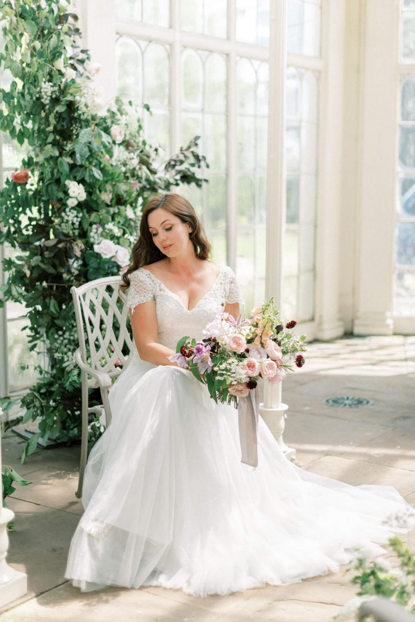 simple natural bride bridal make-up with long loose curls hairstyle for spring and summer; v neck sweetheart neckline wedding gown with full tulle a line skirt and spring wedding bouquet filled with roses, clematis, foxgloves and tied with silk ribbon - Venue: Wollaton Hall Camellia House (cast iron glass house) in Nottinghamshire. Photo by London and Newcastle UK based Filipina fine art light bright and airy wedding and portrait photographer Cristina Ilao, more at www.cristinailao.com