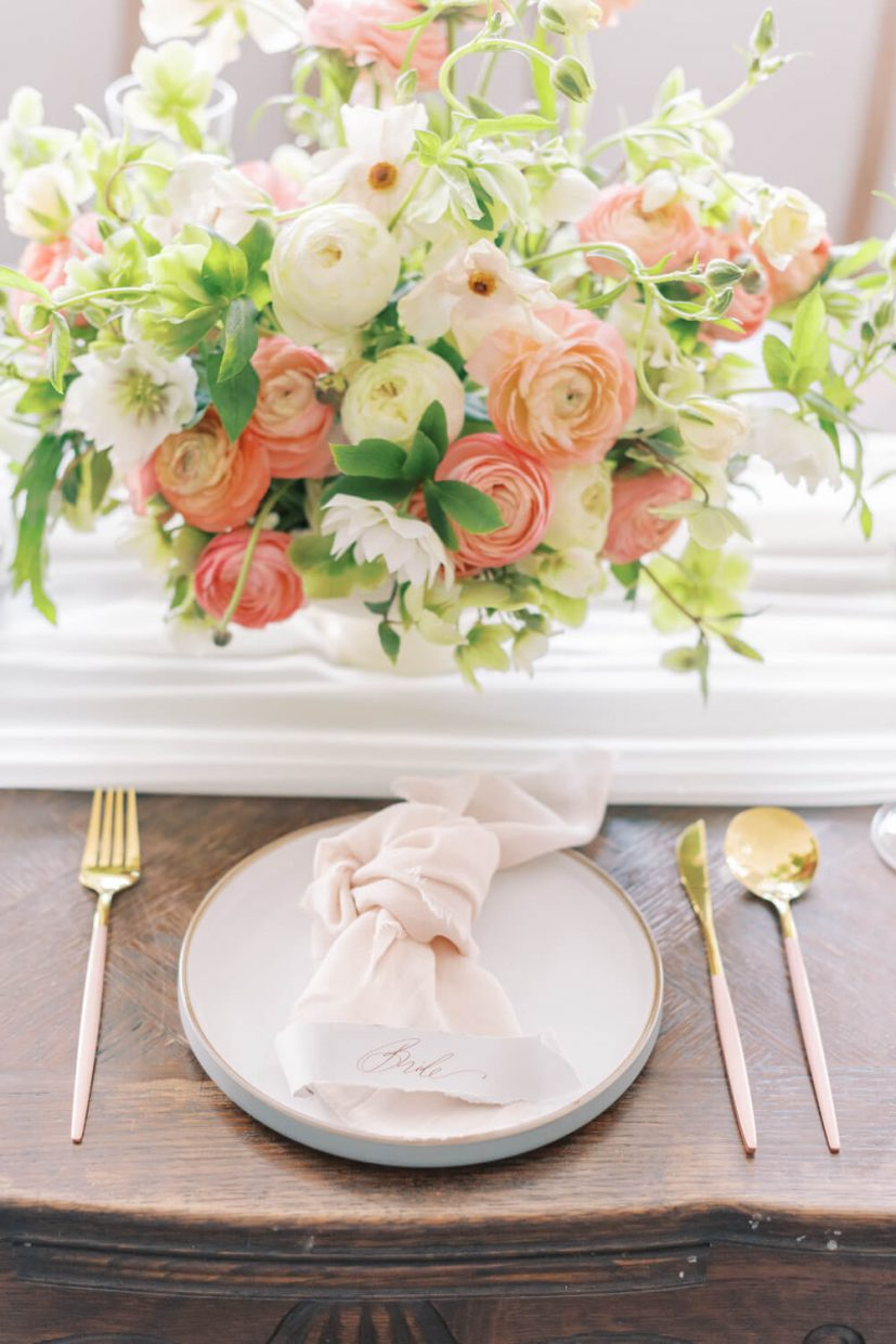 spring and summer bright light and airy wedding table setting with living coral tones. Peach, blush and white ranunculus and green and white hellebores; brass gold cutlery with pink enamel, ceramic plate with blush pink cheese cloth table napkin. Styled by Alexandra Rose Weddings and Photo by Cristina Ilao