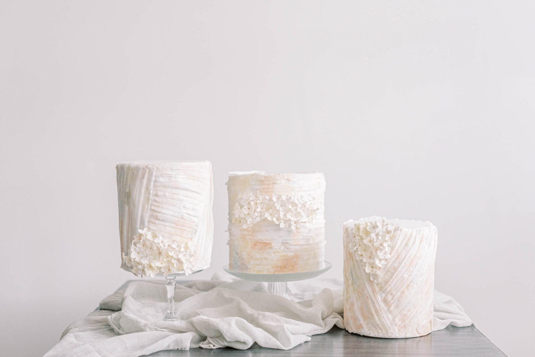 three white simple mini wedding cakes with tiny sugar flowers and wafer designs perfect for intimate microwedding giveaways. styled with cheesecloth on white light a=bright and airy background. Styled by Oxfordshire Wedding Planner Alexandra Rose Weddings and Photo by London Photographer Cristina Ilao