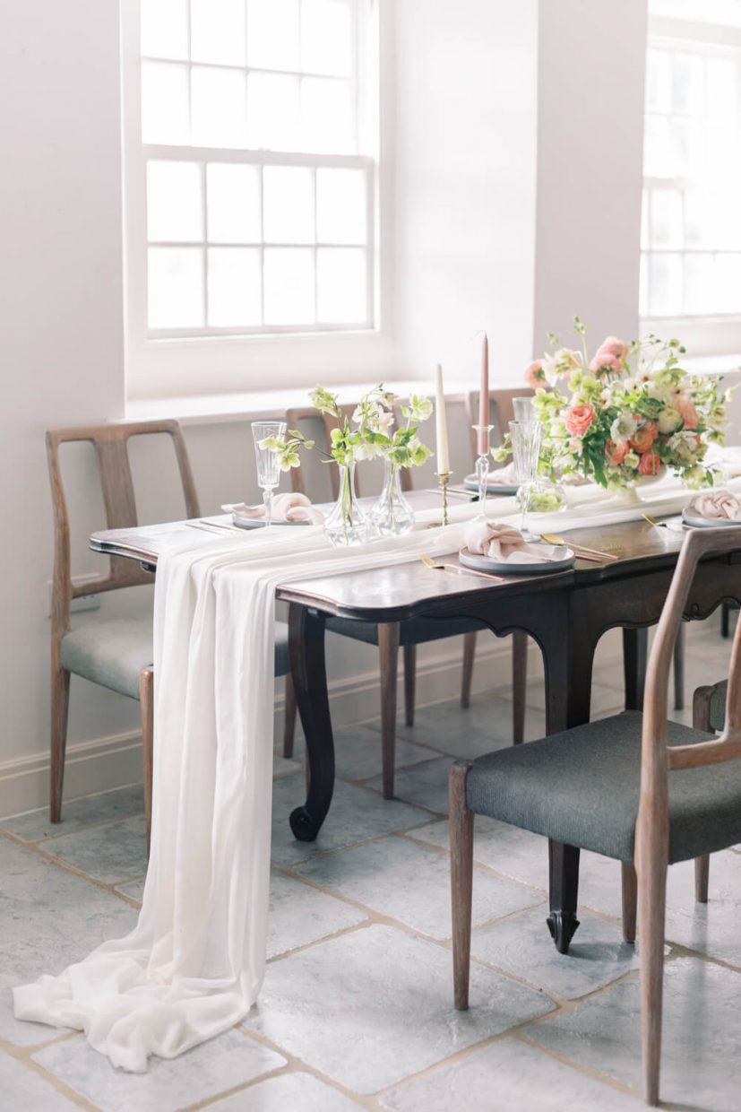 Branding Shoot in Oxford. In photo: simple intimate wedding table setting in Dandridges Mills. Table is decorated with silk table runner, ceramic plates, and seasonal spring flowers hellebores and ranunculus in white peach and pink shades. Shot at light and airy room and wedding venue in Oxfordshire. Styled by Alexandra Rose Weddings and photo by Cristina Ilao Photography