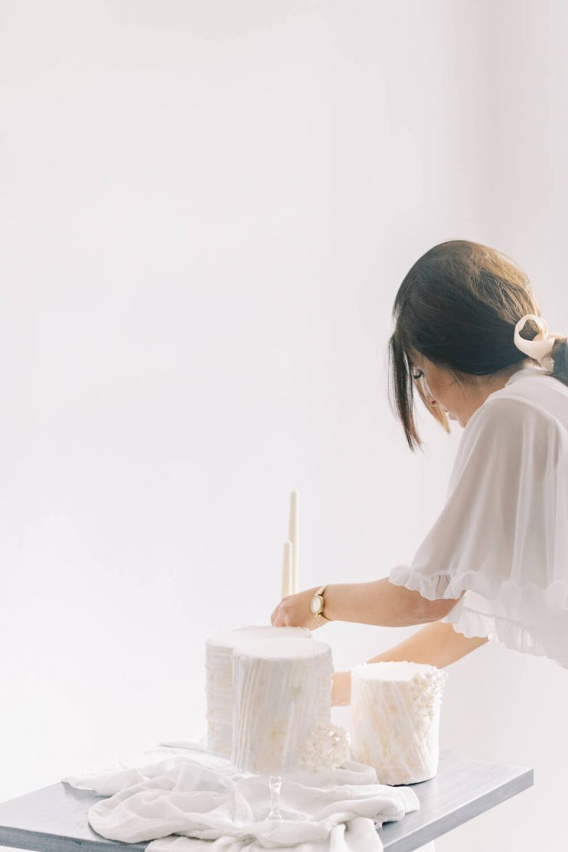 woman in a ponytail and white angel sleeve blouse with mini wedding cakes with sugar flowers and wafer pastel design, ester and erik candles and antique candle holders; light and airy bright white background in wedding venue; Styled by Oxfordshire Wedding Planner Alexandra Rose Weddings and Photo by London Photographer Cristina Ilao