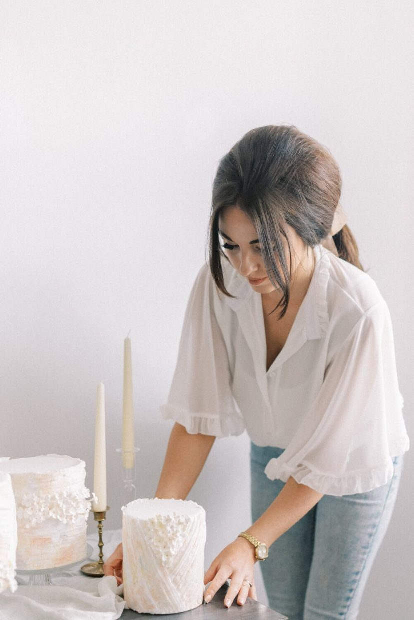 woman in a ponytail and white angel sleeve blouse arranging a mini wedding cake with sugar flowers and wafer pastel design, ester and erik candles and antique candle holders; light and airy bright white background in wedding venue; Styled by Oxfordshire Wedding Planner Alexandra Rose Weddings and Photo by London Photographer Cristina Ilao