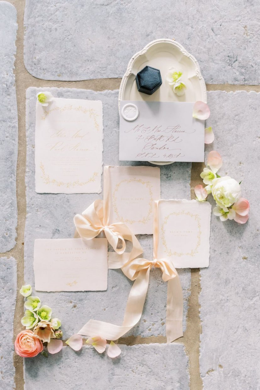 flatlay of wedding invitation with vow books and ribbons, calligraphy on envelope, ring box, petals on a stone floor. Styled by Oxfordshire Wedding Planner Alexandra Rose Weddings and Photo by London Photographer Cristina Ilao