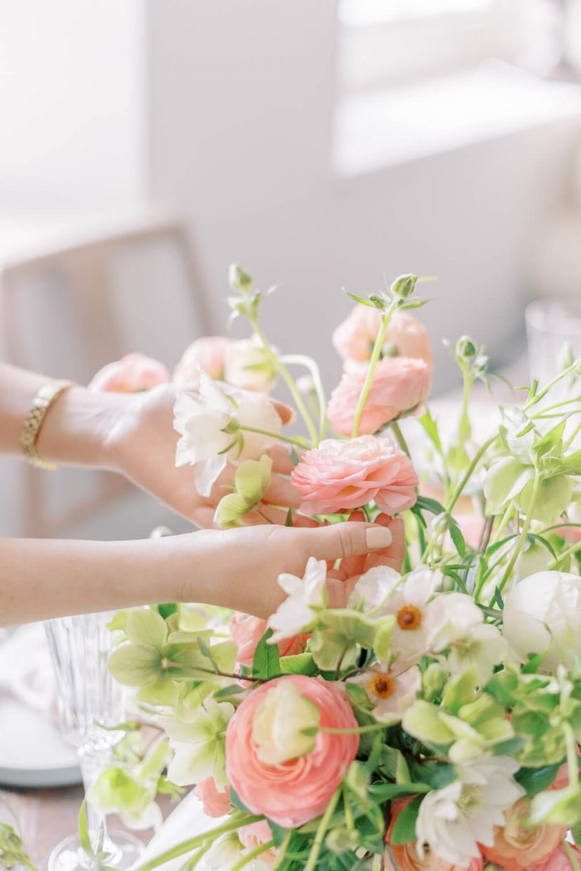 hand holding a flower in spring and summer bright light and airy wedding table setting with living coral tones. Peach, blush and white ranunculus and green and white hellebores; Styled by Alexandra Rose Weddings and Photo by Cristina Ilao