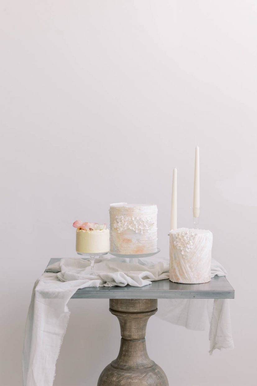 three mini wedding cakes with luxury sugar flowers and wafer layers in pastel colours, peach blue and yellow. styled on a french side table with cheese cloth and ester and erik candles. Styled by Alexandra Rose Weddings and Photo by Cristina Ilao