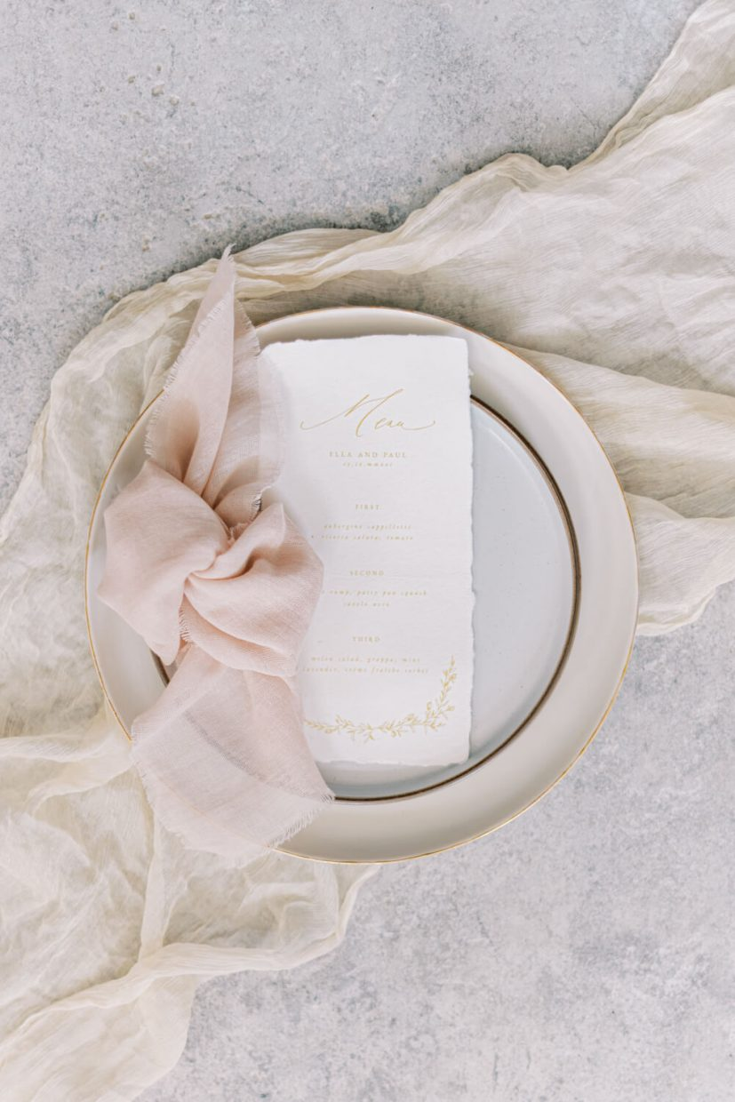 Minimalist flatlay of wedding menu, on ceramic plates and blush pink cheese cloth table napkin and stone floor. Styled by Oxfordshire Wedding Planner Alexandra Rose Weddings and Photo by London Photographer Cristina Ilao