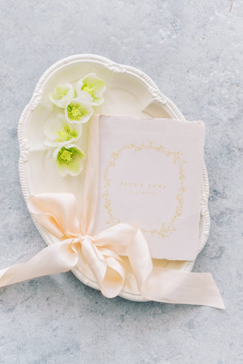 simple wedding stationery flatlay of vow book, tied in silk ribbon, styled with hellebore flowers. branding photo session Styled by Oxfordshire Wedding Planner Alexandra Rose Weddings and Photo by London Photographer Cristina Ilao