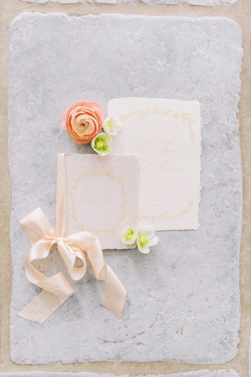 simple wedding stationery flatlay of invitation and vow book, tied in silk ribbon, styled with ranunculus and hellebore flowers. branding photo session Styled by Oxfordshire Wedding Planner Alexandra Rose Weddings and Photo by London Photographer Cristina Ilao
