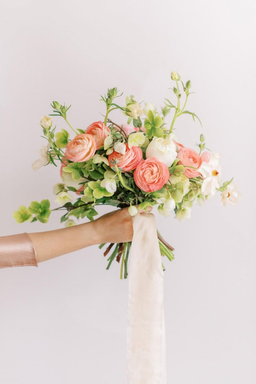 hand holding a beautiful bouquet of wedding flowers for spring and summer, colours include peach, white and green hellebores, ranunculus and silk pale pink ribbon; branding shoot Styled by Oxfordshire Wedding Planner Alexandra Rose Weddings and Photo by London Photographer Cristina Ilao