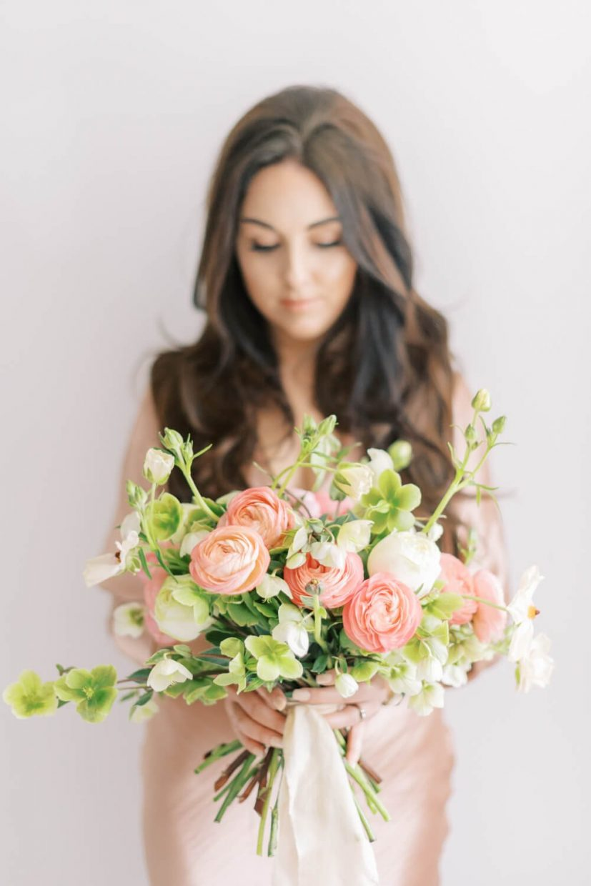 bride holding a srping summer wedding bouquet in shades on peach, white and green, with hellebores, ranunculus, Styled by Oxfordshire Wedding Planner Alexandra Rose Weddings and Photo by London Photographer Cristina Ilao