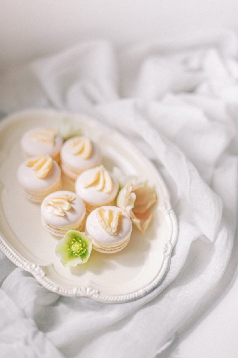 pastel peach bacon flavoured french macarons styled on a white antique plate and cheese cloth with hellebore flowers. Styled by Oxfordshire Wedding Planner Alexandra Rose Weddings and Photo by London Photographer Cristina Ilao