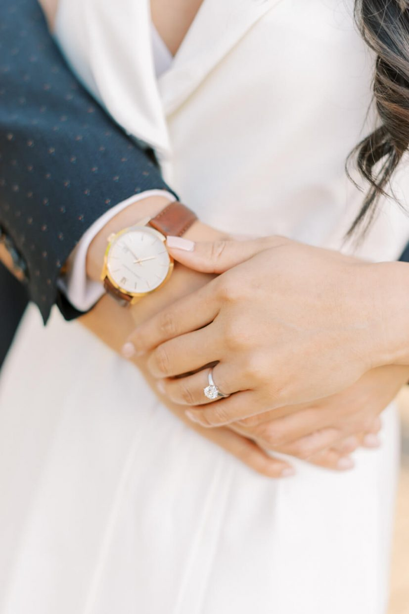 London Engagement Photo Shoot Session in Kensington & Chelsea Old Marylebone Town Hall by Cristina Ilao Fine Art Wedding Photography   In Photo: 1 carat diamond engagement ring on plain platinum band, natural nail polish, simple elegant watch with brown leather strap, white dress