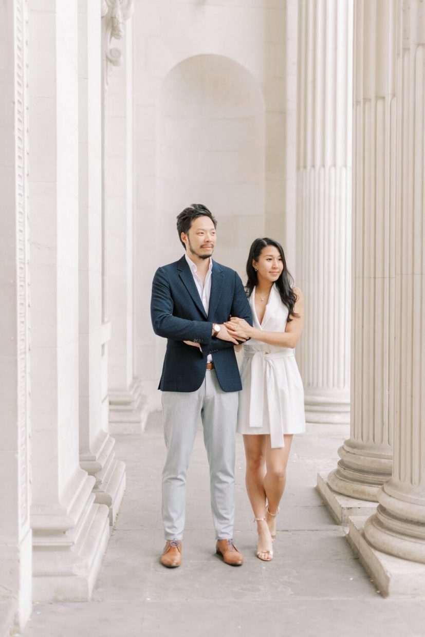 London Engagement Shoot in Kensington & Chelsea Old Marylebone Town Hall by Cristina Ilao Fine Art Wedding Photography   In Photo: South East Asian Chinese couple, civil registry wedding outfit, navy blue suit, grey trousers, brown leather shoes, white mini dress with belt, curled long black hair, natural make-up, gold strappy sandals