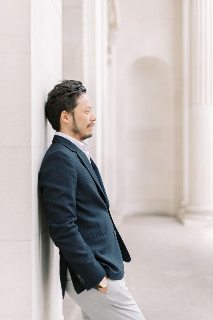 London Engagement Shoot in Kensington & Chelsea Old Marylebone Town Hall by Cristina Ilao Fine Art Wedding Photography   In Photo: Groom's fashion outfit inspiration for small intimate microweddings, navy blue suit, grey trousers paired, natural and fun photos