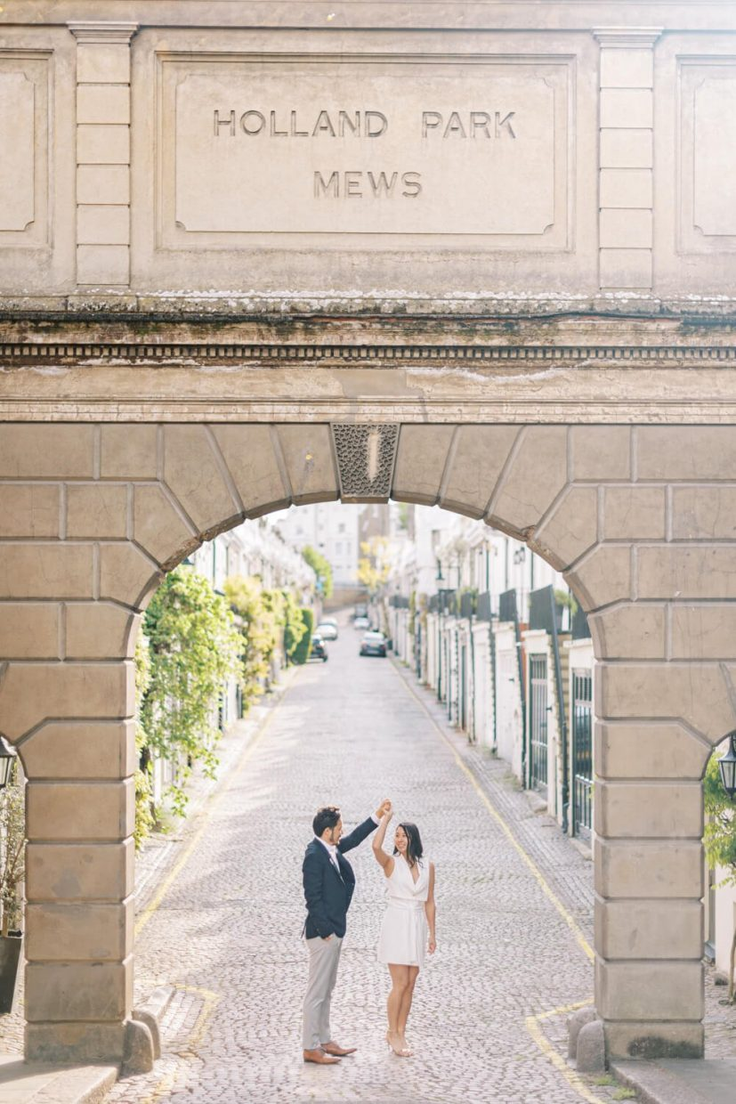 London Engagement Shoot in Holland Park Mews by Cristina Ilao Fine Art Wedding Photography   In Photo: entrance, stone cobblestone road, wedding guest semi formal wear, navy blue suit, grey trousers, brown leather shoes, white mini dress, curled hairstyle, light and airy background, spring summer weather