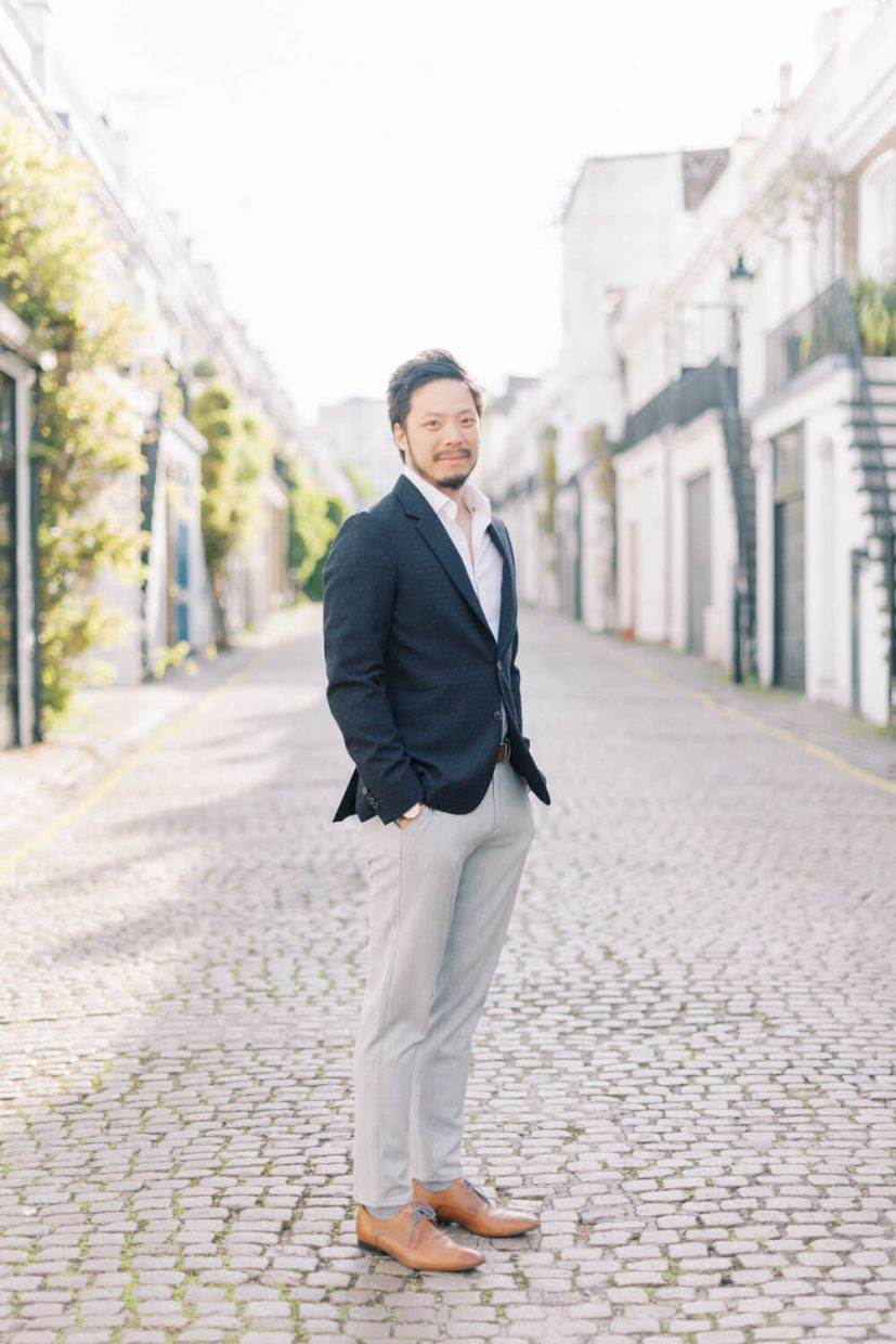 London Engagement Shoot in Holland Park by Cristina Ilao Fine Art Wedding Photography   In Photo: Asian Chinese groom, navy blue suit, white dress shirt, grey trousers, brown leather shoes, light and airy background