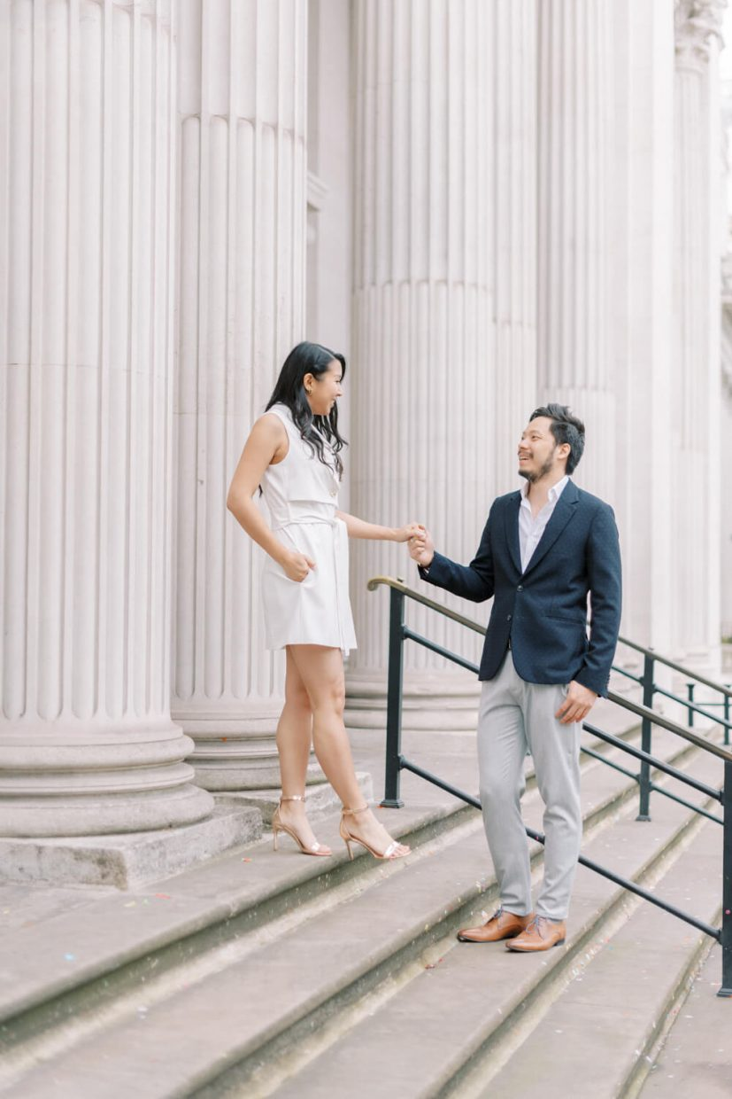 London Engagement Shoot in Old Marylebone Town Hall by Cristina Ilao Fine Art Wedding Photography   In Photo: Asian Chinese engaged couple, white mini dress, rose gold strappy high heels, navy blue suit and grey trousers, brown leather shoes, white pillars