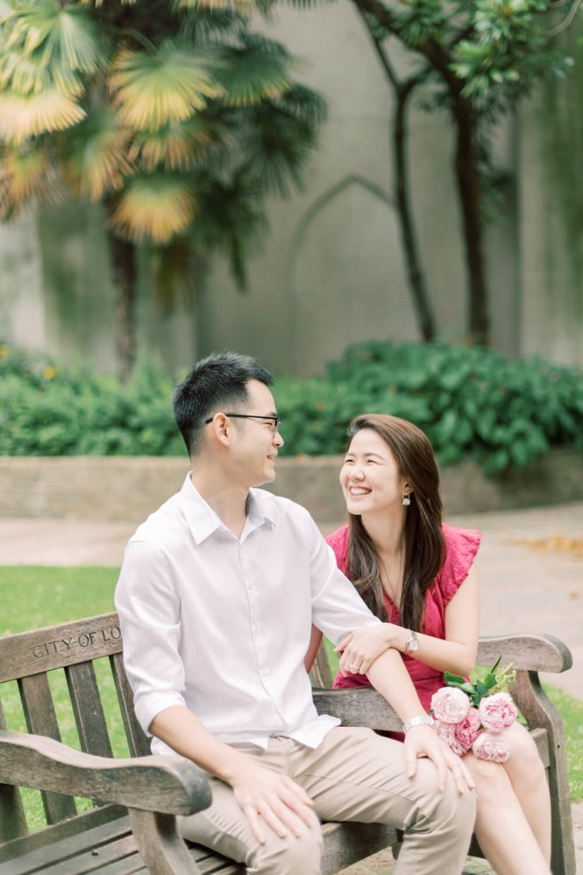 London St Dunstan in the East Engagement Session with Cristina Ilao Photography   In Photo: Asian couple sitting on a wooden bench, bride wearing a pink mini dress and nude platform sandals and holding rose and deep pink peonies, groom wearing a white dress shirt with khaki trouser pants