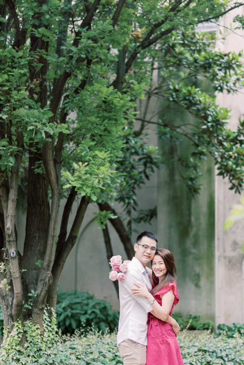 London St Dunstan in the East Engagement Session with Cristina Ilao Photography   In Photo: Asian Singaporean Chinese couple laughing in front of trees and beautiful architecture and big leafy plants, bride wearing a pink mini dress and nude platform sandals and holding rose and deep pink peonies, groom wearing a white dress shirt with khaki trouser pants