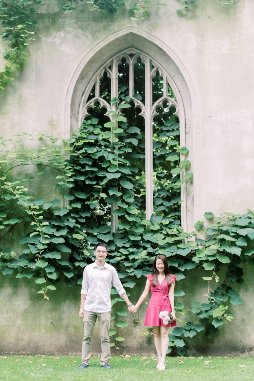 London St Dunstan in the East Engagement Session with Cristina Ilao Photography   In Photo: Asian Singaporean Chinese couple standing at the entrance in front of beautiful architecture and big leafy plants, bride wearing a pink mini dress and nude platform sandals and holding rose and deep pink peonies, groom wearing a white dress shirt with khaki trouser pants