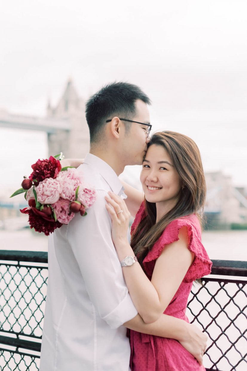 London Tower Bridge Engagement Session with Cristina Ilao Photography   In Photo: Asian Singaporean Chinese couple kissing and hugging with the Thames River, black wire fence and Tower bridge in the background, bride wearing a pink mini dress and holding rose and deep pink peonies, groom wearing a white dress cotton shirt