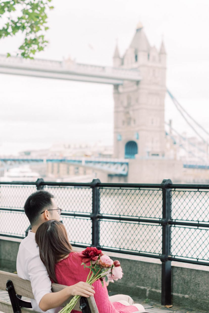 London Tower Bridge Engagement Session with Cristina Ilao Photography   In Photo: Asian Singaporean Chinese couple sitting on a bench and facing the Thames River, black wire fence and Tower bridge in the background, bride wearing a pink mini dress and nude platform sandals and holding rose and deep pink peonies, groom wearing a white dress shirt with khaki trouser pants