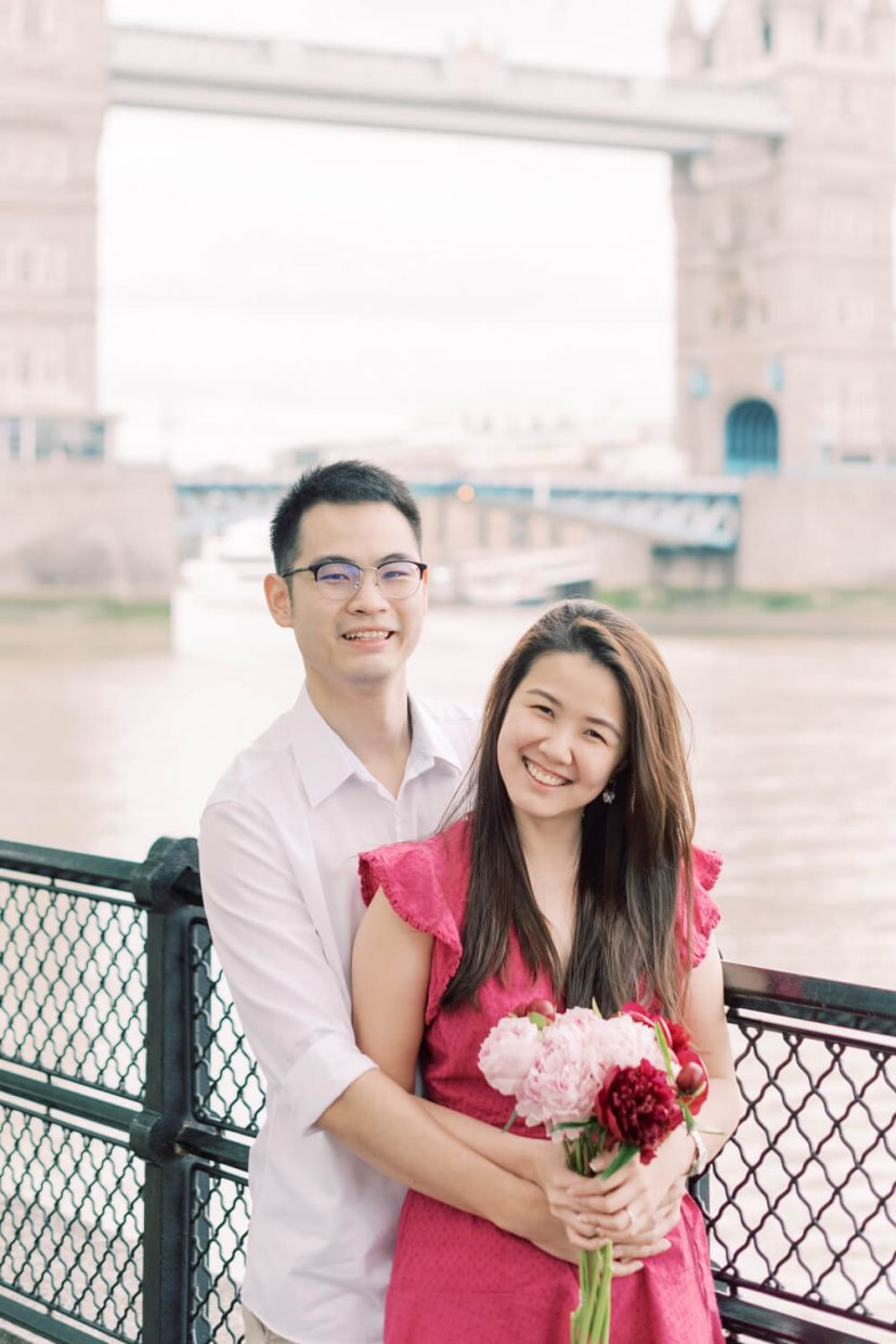 London Tower Bridge Engagement Session with Cristina Ilao Photography   In Photo: Asian Singaporean Chinese couple smiling and having fun with the Thames River, black wire fence and Tower bridge in the background, bride wearing a pink mini dress and nude platform sandals and holding rose and deep pink peonies, groom wearing a white dress shirt with khaki trouser pants