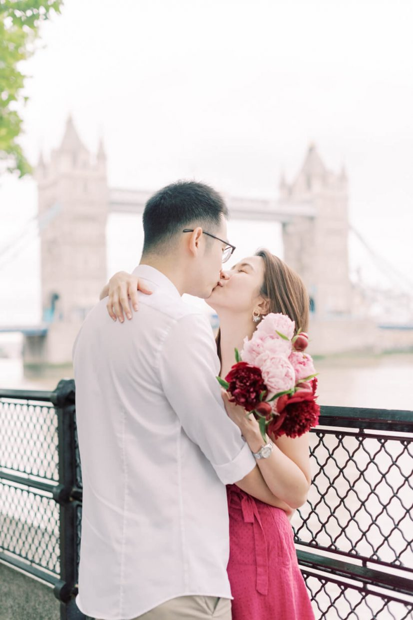 London Tower Bridge Engagement Session with Cristina Ilao Photography   In Photo: Asian Singaporean Chinese couple kissing with the Thames River, black wire fence and Tower bridge in the background, bride wearing a pink mini dress and nude platform sandals and holding rose and deep pink peonies, groom wearing a white dress shirt with khaki trouser pants